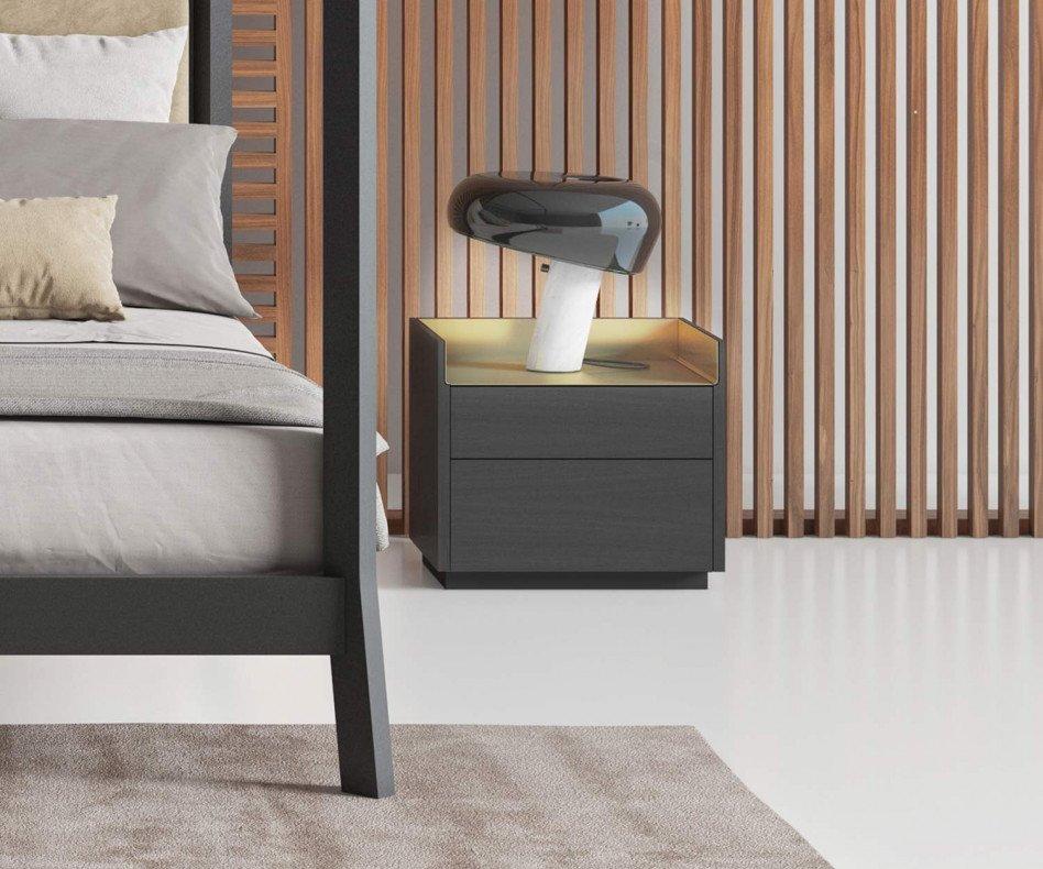 Exklusiver Design Nachttisch mit Nachttischlampe neben Bett im Schlafzimmer furniert