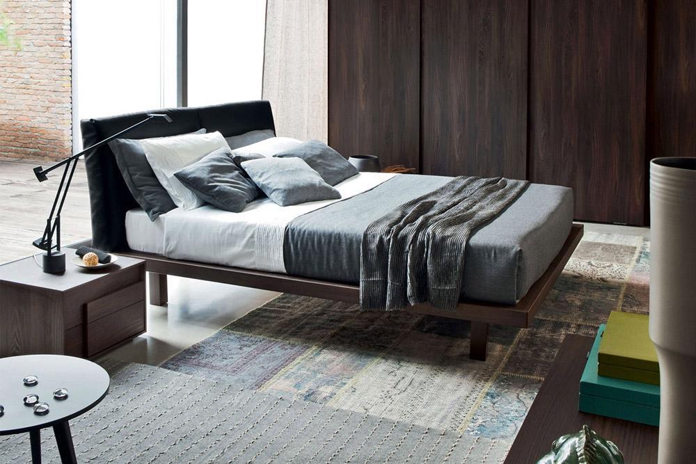 Das Novamobili Bett Nido hat einen Holzrahmen und ein gepolstertes Kopfteil aus schwarzen Echtleder.